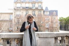 Half African tourist listening to new songs in earphones with sm. Tourist raving with white in ear headphones and smartphone near Eiffel tower. Jocund guy Stock Photo