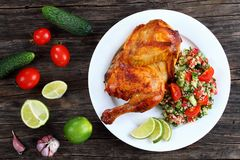 Half of appetizing grilled juicy chicken. Half of appetizing roasted juicy chicken with golden brown crust served with lime slices and couscous vegetable salad Royalty Free Stock Images