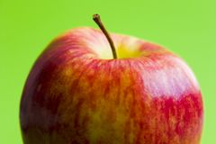 Half Apple. Half red apple on green background royalty free stock images