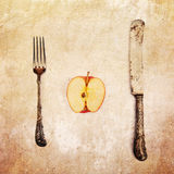 Half of an apple with antique cutlery Royalty Free Stock Photos