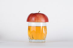 Half apple on the glass. Half red apple on the glass with apple juice on the white background Stock Images