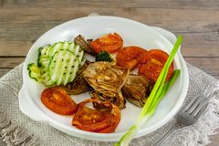 Half of an artichoke on the grill with slices of cucumber and ripe red tomato on a white plate with Brussels sprouts and Royalty Free Stock Images