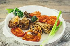 Half artichoke, grilled and served with slices of ripe red tomatoes, Brussels sprouts and green onions on a white plate on a woode. N background in rustic style Stock Photography