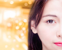 Half of Asian woman`s face on golden background stock images