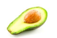 Half Avocado. Single halved dark green avocado fruit showing the kernel on a white background Stock Photos