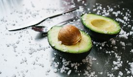 Half an avocado on background of a steel table, fresh healthy food breakfast on kitchen, green vegan diet, nature omega with salt royalty free stock photography