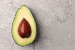 Half avocado with seed on cement background top view stock photography