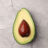 Half avocado with seed on cement background top view stock photo