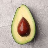 Half avocado with seed on cement background top view royalty free stock photography