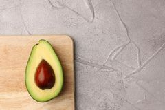 Half avocado with seed on wooden board. avocado on cement top view royalty free stock images