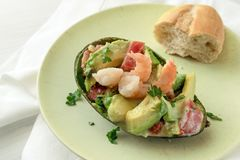 Half avocado stuffed with tomato, shrimp and parsley garnish wit. H a bun on a light green plate, appetizer snack, white tablecloth background with copy space royalty free stock images