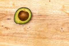 Half Avocado. A half avocado in wooden table Royalty Free Stock Photos