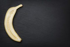 Half banana cut through on slate. Stock Images