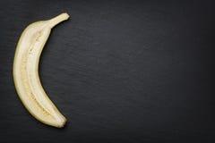 Half banana cut through on slate. Stock Images