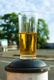 Half a beer left on a post in the street Stock Image