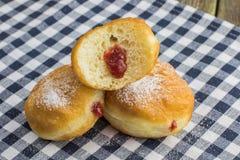 Half berliner (doughnut) with strawberry jam Royalty Free Stock Photography