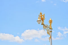 Half-bird half-woman on street lamp. On blue sky background Stock Image