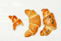 Half bitten baked yeast bread roll croissants with black and white sesame royalty free stock images