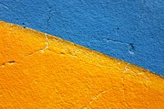 Half of blue and half of yellow painted grunge wall for backgroud. Half of blue and half of yellow painted grunge wall without gradient for backgrounds Royalty Free Stock Photo