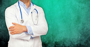 Half body of a doctor with crossed arms. On green background Stock Images
