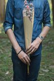 Half body of man in blue jean shirt hand hold flower. Bouquet Stock Photography