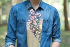 Half body of man in blue jean shirt hand hold flower in middle c. Heast Royalty Free Stock Photos