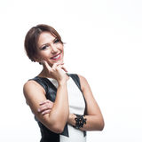 Happy fashionable young woman. Half body portrait of happy fashionable young woman in black and white leather dress, studio background Royalty Free Stock Image