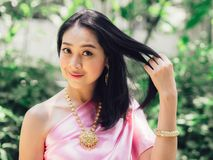 Half body portrait of Thai woman in Thai traditional custome. Half body portrait of Thai woman in Thai traditional custome stand in the garden royalty free stock image