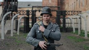 Portrait of a sad German soldier standing in front of a concentration camp. The Second World War reenactment stock video