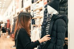 Half body shot of a happy asian young woman with shoulder bag looking at clothes hanging on the rail inside the clothing shop. Royalty Free Stock Image
