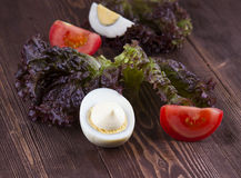 Half of boil egg handful of mayonnaise. egg, tomato, lettuce on. A wooden background royalty free stock photography