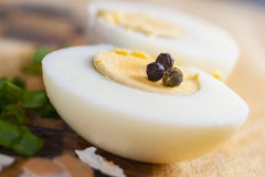Half of boiled egg  prepared on cutting board. With grains of pepper and Stock Photos