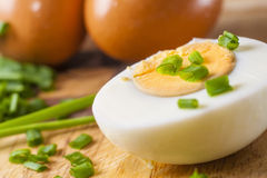 Half of boiled egg  prepared on cutting board. With sliced chive and two whole eggs in background Stock Photo