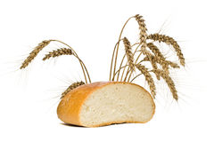 Half of the bread loaf and wheat spikes, isolated Royalty Free Stock Photos