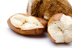 Half a bread with lye bread roll. On white background Stock Photo