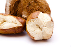 Half a bread with lye bread roll. On white background Stock Photos