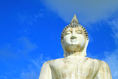 Half buddha statue on blue sky Stock Images