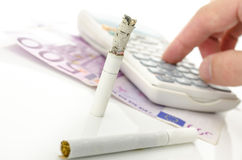 Half burned cigarette with calculator and Euro money Royalty Free Stock Photography