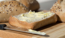 Half a Buttered Ciabatta Bread Roll with Knife. Stock Image