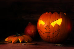 Half carved halloween pumpkin with glowing eyes on dark rustic w Royalty Free Stock Images