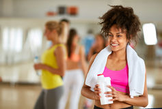 Half-caste female refreshing with protein shake. Young half-caste female smiling and refreshing with protein shake after workout at gym Royalty Free Stock Photography