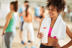 Half-caste girl with protein shake after training. Happy young half-caste girl drink protein shake after training in fitness center Stock Photography