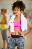 Half-caste woman with towel and bottle of protein shake after tr. Young fit half-caste with towel and bottle of protein shake after hard training at gym Royalty Free Stock Photos