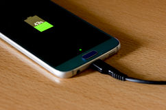 A half-charged mobile phone. On top of the table Royalty Free Stock Image