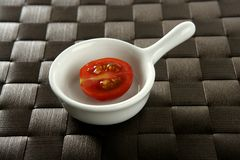 Half cherry tomato in a little dish Royalty Free Stock Image