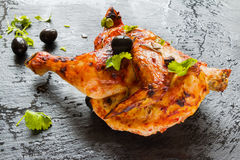 Half of chicken, baked in oven with black olives in oil, fresh parsley, stone background Stock Photo