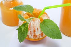 Half-cleared orange fruit with mint leaves, cocktail concept,  on gray Royalty Free Stock Image