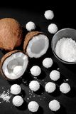 Half a coconut and a lot of coconut candy on a black background. royalty free stock images