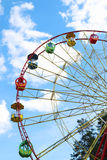 Half of colorful Ferris wheel and tops of trees and blue sky Royalty Free Stock Photos