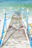 Half concrete and woooden pier with blue ropes leading into the Stock Photography